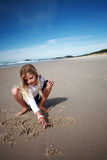 Girl drawing in beach sand Royalty Free Stock Photos