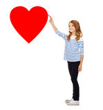 Girl drawing big red heart in the air Stock Photography