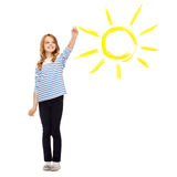 Girl drawing big sun in the air. Education, school and happy people concept - cute little girl drawing big sun in the air Stock Photo