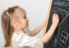 Girl drawing on the blackboard Royalty Free Stock Images