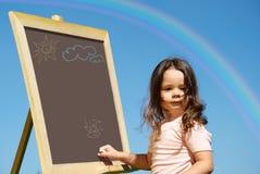 Girl drawing on blackboard Stock Image