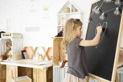 Girl drawing on blackboard stock photography