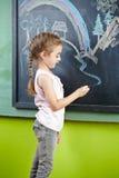 Girl drawing on bloackboard Stock Images