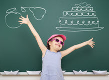 Girl drawing cake and fruit on school board Stock Photos