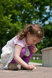 Girl drawing with chalk Stock Image