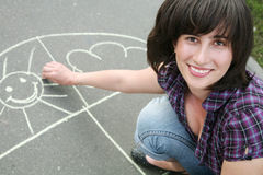 Girl drawing a chalk on asphalt Royalty Free Stock Photos