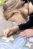 Girl drawing with chalk on pavement Royalty Free Stock Photo