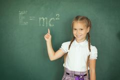 Girl drawing on chalkboard formula e mc2. Education and school concept.  stock photos