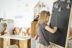 Girl drawing on chalkboard. With lightbulbs in warm interior with toys and wooden desk stock photography