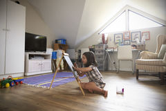 Girl Drawing On Chalkboard In Playroom Stock Photo