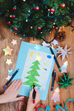 Girl drawing Christmas card with pine tree Royalty Free Stock Photos