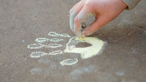 Girl drawing with colored chalk on the pavement Stock Image
