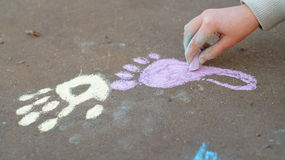 Girl drawing with colored chalk on the pavement Stock Images