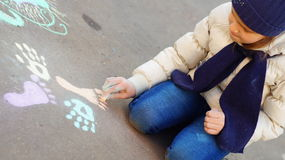 Girl drawing with colored chalk on the pavement Stock Photo