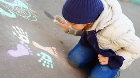 Girl drawing with colored chalk on the pavement Royalty Free Stock Image
