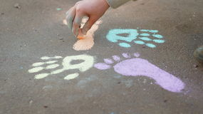 Girl drawing with colored chalk on the pavement Royalty Free Stock Images
