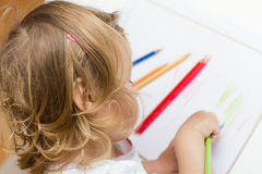 Girl drawing with colored pencils. Little girl drawing with colorful crayons at home Stock Photography