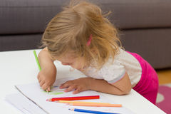 Girl drawing with colored pencils. Little girl drawing with colorful crayons at home Royalty Free Stock Photography