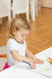 Girl drawing with colored pencils. Little girl drawing with colorful crayons at home Stock Image