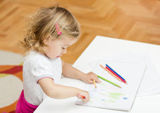 Girl drawing with colored pencils. Little girl drawing with colorful crayons at home Stock Images