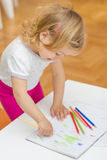 Girl drawing with colored pencils. Little girl drawing with colorful crayons at home Royalty Free Stock Photo