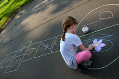 A girl drawing a colorful hopscotch. A girl with ponytail drawing colorful hopscotch in pink leggins Stock Image