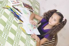 Girl drawing with crayons Stock Images