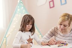 Girl drawing with crayons. Mother and daughter playing in a play room, drawing with crayons. Focus on the daughter royalty free stock photography