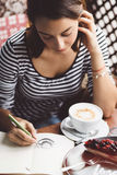 Girl drawing a cup of coffee Royalty Free Stock Image