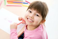 Girl is drawing. Cute little girl is drawing with felt-tip pen in preschool stock photo
