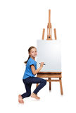 Girl drawing on easel Royalty Free Stock Image