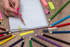 Girl drawing on empty note with colorful pencils Stock Images