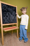 Girl drawing family on blackboard Stock Image