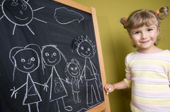 Girl drawing family on blackboard Royalty Free Stock Image
