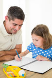 Girl drawing while father sitting by Royalty Free Stock Photo