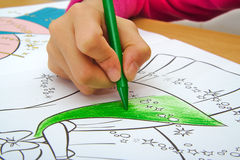 Girl drawing with a green crayon in classroom Royalty Free Stock Photography