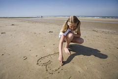 Girl drawing a heart. Puppy love, girl drawing a heart in the sand at the beach stock photography