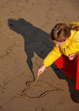 Girl drawing a heart. Young girl drawing a heart in the sand with a stick at the Adriatic beach royalty free stock image