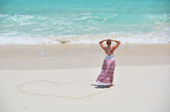 Girl drawing a heart on the beach Stock Photos
