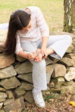 Girl drawing heart on her sole. Of bare foot while sitting on stone wall Royalty Free Stock Images