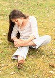 Girl drawing heart on her sole. Barefoot girl drawing heart on her sole of bare foot while sitting on stone wall Royalty Free Stock Photo