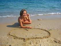 Girl drawing heart on sand Royalty Free Stock Photo
