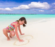 Girl drawing heart on sand Royalty Free Stock Photos