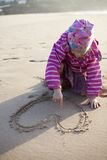 Girl drawing a heart in sand Royalty Free Stock Photos