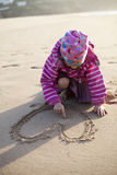 Girl drawing a heart in sand Royalty Free Stock Photography