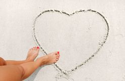 Girl is drawing heart on the sand. Stock Image