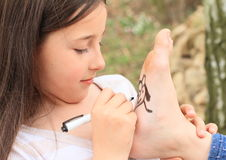 Girl drawing hearts on sole. Of bare foot of another girl Royalty Free Stock Images