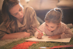 Girl drawing with her mother. Stock Images