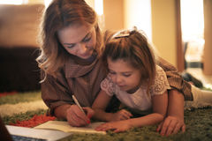 Girl drawing with her mother. Stock Image