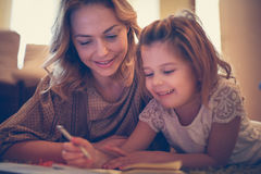 Girl drawing with her mother. Stock Photo